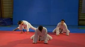 Tre unga män som bär karatekimonon som gör sträckning, övar på idrottshallen arkivfilmer