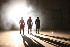 Tre unga män som boxas genomkörare i en gammal byggnad Royaltyfri Foto