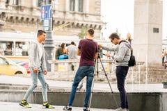Tre unga män som filmar sig på stadsfyrkanten i den Budapest Ungern Arkivbild