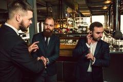 Tre unga män står i bar En hållhand på headphonen Han visar upp fingret Andra blick för ung man först och att försöka till royaltyfri fotografi