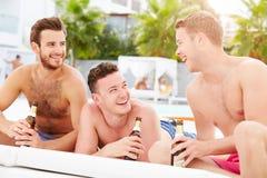 Tre unga manliga vänner på ferie vid pölen tillsammans Arkivbild