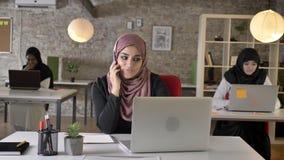Tre unga muslimkvinna i hijabsammanträde och arbete i det moderna kontoret, härlig muslimkvinna som talar på telefonen stock video
