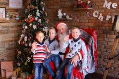 Tre unga pojkar berättar Santa Claus roliga berättelser som in in dekoreras Royaltyfri Bild