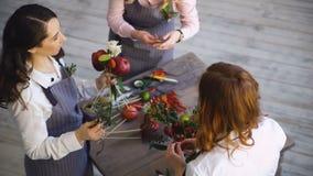 Tre unga stiliga kockblomsterhandlare arbetar på buketten för frukt och för grönsaken för blommafruktaffärdanande