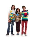 Tre unga studenter som tillsammans står och ler Royaltyfri Foto
