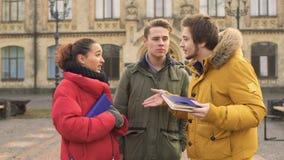 Tre unga studentsamtal near universitetet arkivfilmer