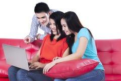 Tre unga tonåringar som ser bärbara datorn Arkivbild