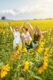 Tre unga vänner i ett solrosfält Arkivbild