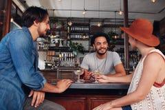 Tre unga vänner på kafét som har drinkar tillsammans Royaltyfri Bild