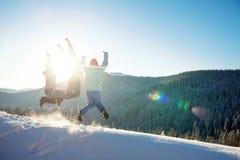 Tre unga vänner som hoppar och har gyckel på det snöig berget arkivbilder