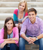 Tre unga vänner som tillsammans sitter Fotografering för Bildbyråer