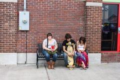 Tre unga vuxna människor som sitter på en stads- bänk Tulsa Oklahoma USA circa Maj 2010 Royaltyfri Fotografi