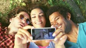 Tre unga vuxna människor som tar en selfie som ligger på gräset lager videofilmer