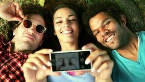 Tre unga vuxna människor som tar en selfie som ligger på gräset stock video