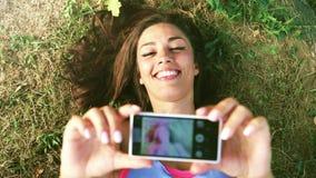 Tre unga vuxna människor som tar en selfie som ligger på gräset arkivfilmer
