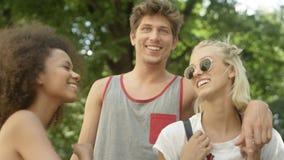 Tre unga vuxna vänner som har gyckel i en stad, parkerar Royaltyfria Bilder