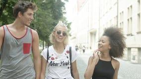 Tre unga vuxna vänner som har gyckel i en stad, parkerar Royaltyfri Bild