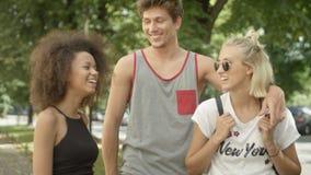 Tre unga vuxna vänner som har gyckel i en stad, parkerar Royaltyfri Foto