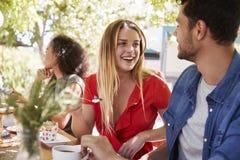 Tre unga vuxna vänner som utomhus äter middag på en tabell royaltyfri fotografi