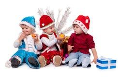 Tre ungar i Santa hattar Fotografering för Bildbyråer