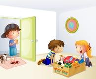 Tre ungar inom huset med en ask av leksaker Arkivfoton