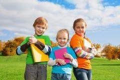 Tre ungar med böcker i park Royaltyfri Foto