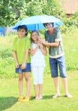 Tre ungar med det blåa paraplyet Arkivbild