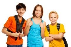Tre ungar med skolar ryggsäckar Arkivbilder
