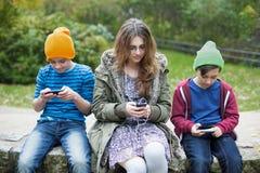 Tre ungar med telefoner Fotografering för Bildbyråer