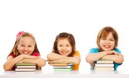 Tre smart ungar på hög av bokar Royaltyfri Foto