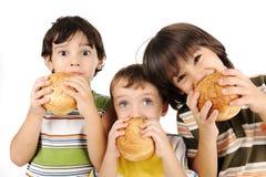 Tre ungar som äter hamburgare royaltyfri bild