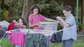 Tre ungar som av tar tvätterit från den hängande linjen till korgen stock video