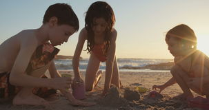 Tre ungar som bygger sandslottar på stranden under solnedgång