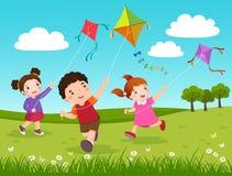 Tre ungar som flyger drakar i parkera