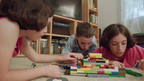 Tre ungar som hemma spelar med legotegelstenar arkivfilmer