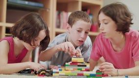 Tre ungar som hemma spelar med legotegelstenar lager videofilmer