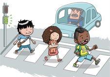 Tre ungar som korsar gatan genom att använda övergångsstället Arkivbild