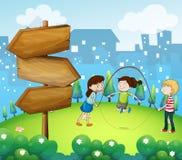 Tre ungar som spelar i trädgården med träpilar Royaltyfri Foto