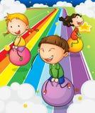 Tre ungar som spelar med studsa, klumpa ihop sig på den färgrika vägen Arkivbild