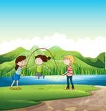 Tre ungar som spelar nära floden Arkivbilder