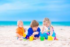 Tre ungar som spelar på en strand royaltyfri foto