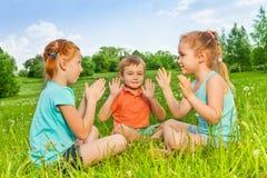 Tre ungar som spelar på ett gräs Arkivfoton