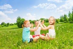 Tre ungar som spelar på ett gräs Arkivfoto