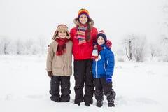 Tre ungar som tillsammans står på vintersnö Royaltyfri Foto