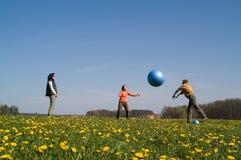 Tre ungdomar med bollen Arkivfoto