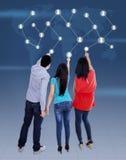 Tre ungdomarsom trycker på en pekskärm Fotografering för Bildbyråer