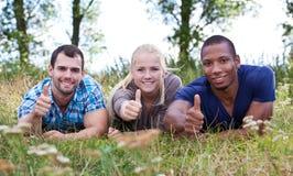 Tre ungdomarsom visar upp tummar Arkivbild