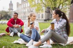 Tre ungkarlstudenter som tillsammans tycker om kaffeavbrottet royaltyfri foto