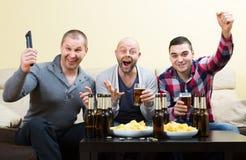 Tre uomini che guardano calcio con birra dell'interno Fotografie Stock Libere da Diritti
