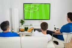 Tre uomini che guardano la partita di calcio Fotografia Stock Libera da Diritti